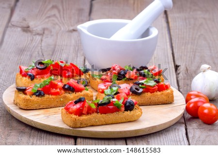 Delicious italian appetizer bruschetta on a cutting board with mortar with pestle, tomatoes and garlic - stock photo