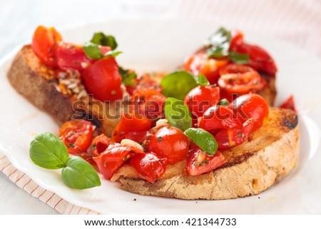 Delicious Italian bruschetta with cherry tomatoes, basil and garlic. - stock photo