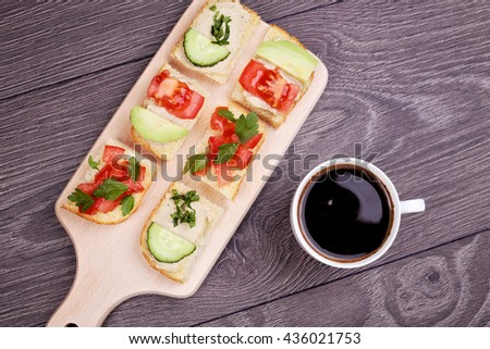Delicious Italian bruschetta with tomato, cucumber, chick-pea paste, parsley and avocado slices on white bread on the wooden board next to cup of strong black coffee, top view - stock photo