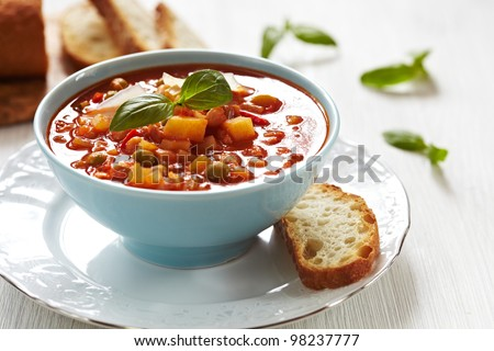 Delicious Italian minestrone soup with bread - stock photo