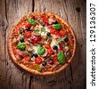 Delicious italian pizza served on wooden table - stock photo