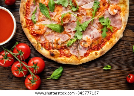 Delicious italian pizza served on wooden table, shot from above  - stock photo