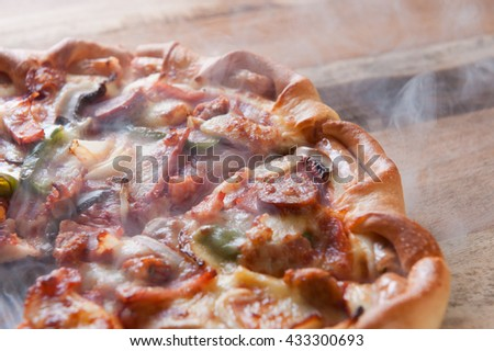 delicious italian pizza served on wooden table with smoke.  - stock photo