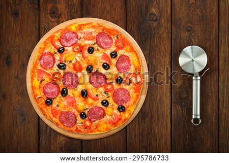 Delicious italian pizza with salami pepperoni, mushrooms and black olives - thin pastry crust at wooden table background with stainless steel cutter, above view - stock photo