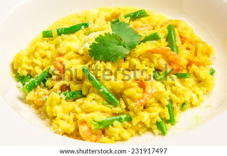Delicious italian risotto with shrimps,  green beans, feta and parmesan, served on a white plate - stock photo