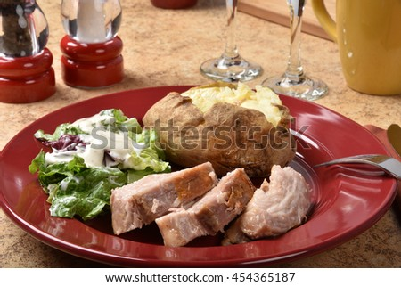 Delicious juicy pork belly with salad and a baked potato - stock photo
