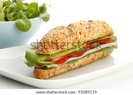 Delicious large submarine sandwich with ham, lettuce, tomatoes and cucumbers on white background - stock photo