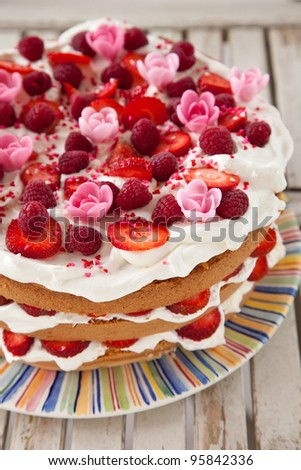 Delicious layered birthday cake dressed with fruit, whipped cream and marzipan flowers - stock photo