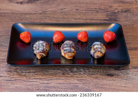 Delicious little chocolat croissants with strawberries and sugar  - stock photo