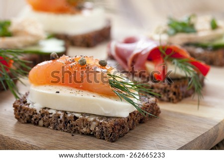 Delicious little sandwiches with tuna, cheese, prosciutto and vegetables. Zoom and macro shots  - stock photo