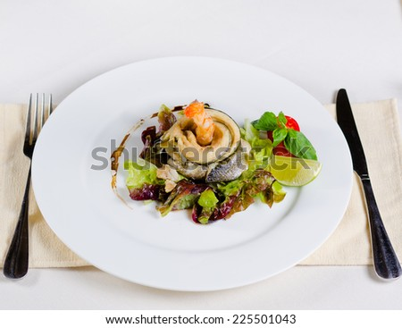 Delicious Main Dish of Fish and Shrimp Meat and Veggies Combination in Stylish Plating on White Round Plate with Fork and Knife on Sides. - stock photo