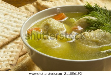 Delicious Matzoh ball soup with crackers wine and dill - stock photo