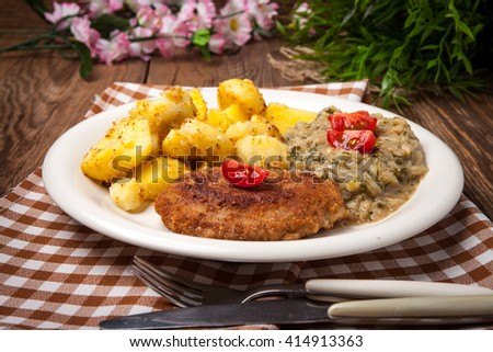 Delicious meal of minced meat cutlet, potatoes and fried cabbage. Selective focus. - stock photo