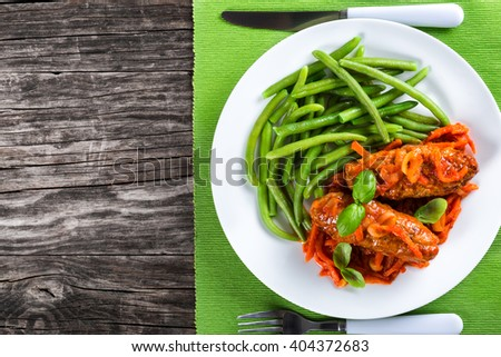 Delicious Meat Cutlets stewed with onion, carrot tomato sauce, decorated with basil leaves in a white dish with boiled green bean on a table napkin with fork and knife, top view - stock photo