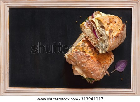Delicious meat sandwiches and some spices on chalk blackboard with copy space for text. - stock photo