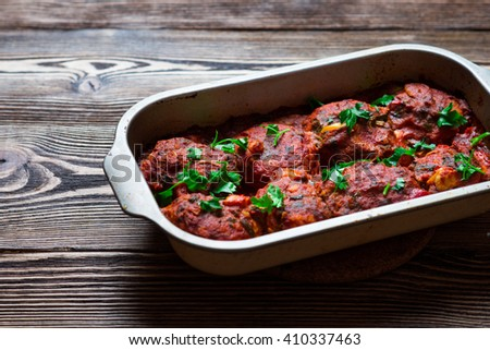 Delicious meatballs in a spicy tomato sauce on wooden background - stock photo