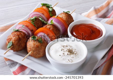 Delicious meatballs on skewers with sauce on a plate close-up. horizontal  - stock photo