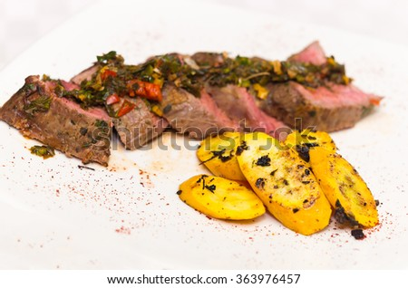 Delicious medallions of tenderloin steak placed upon white dinner plate with some vegetables next to it, elegant presentation - stock photo