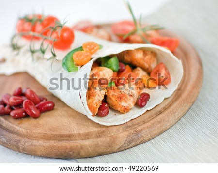 Delicious mexican wrap with chicken stripes and vegetable - stock photo