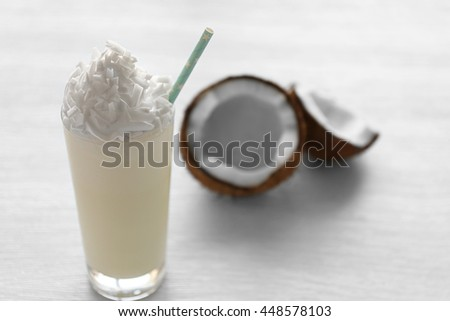 Delicious milkshake with coconut on wooden table - stock photo