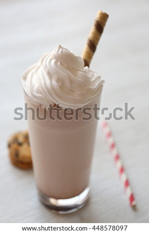 Delicious milkshake with cookies on wooden table - stock photo