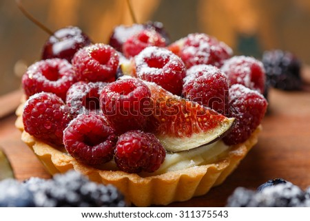 Delicious mini tart with fresh berries and custard on wooden background - stock photo