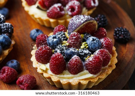 Delicious mini tarts with fresh berries and custard on wooden background - stock photo