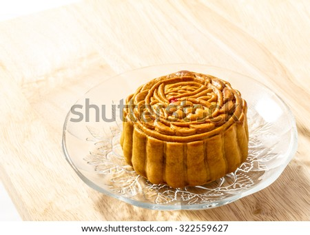 Delicious mooncake in a clear glass plate placed on wood background. - stock photo
