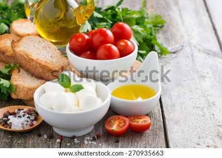 delicious mozzarella and ingredients for a salad on wooden table, horizontal - stock photo