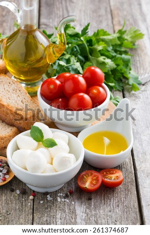 delicious mozzarella and ingredients for a salad, vertical, close-up - stock photo