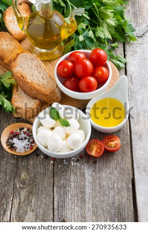 delicious mozzarella and ingredients for the salad on a wooden background, top view, vertical - stock photo