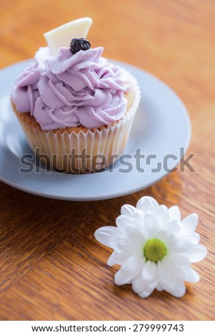 Delicious muffin with blueberry cream and white chocolate on top - stock photo
