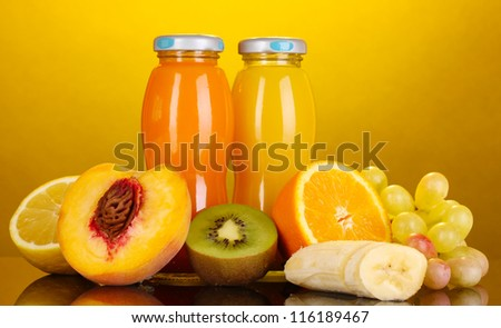 Delicious multifruit juice in a bottle and fruit next to it on yellow background - stock photo