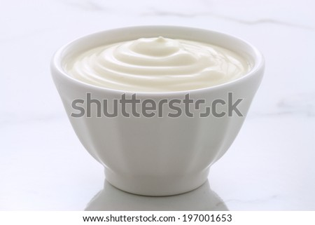 Delicious, nutritious and healthy fresh plain yogurt on vintage italian carrara marble setting. - stock photo
