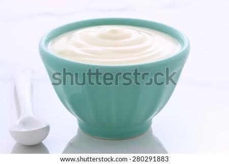 Delicious, nutritious and healthy fresh plain yogurt on vintage italian carrara marble setting. - stock photo
