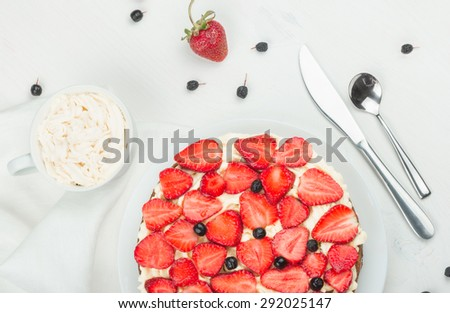 Delicious nutritious cake with fresh strawberries decorated with chokeberry, white cup with whipped cream, steel spoon, strawberry, napkin, knife,  plate, top view,  good morning - stock photo
