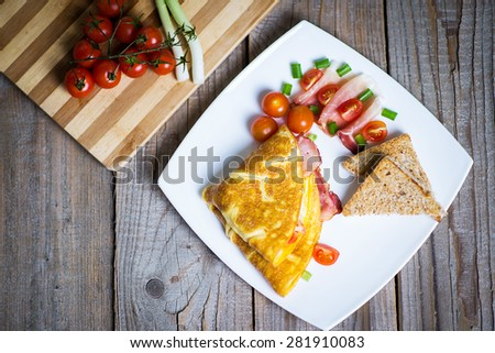 Delicious omelette with vegetables on a plate; ham and chees ome - stock photo