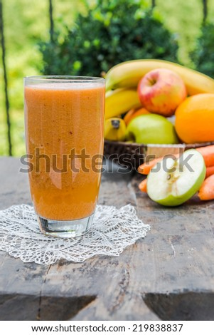 Delicious orange, apple, carrot and banana smoothie  - stock photo