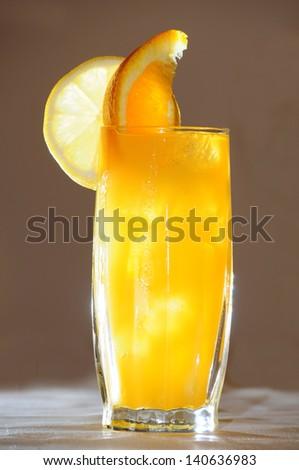 Delicious orange cocktail isolated on beige background - stock photo