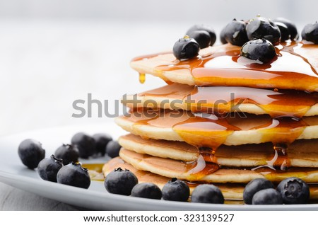 Delicious pancakes close up, with fresh blueberries and maple syrup - stock photo