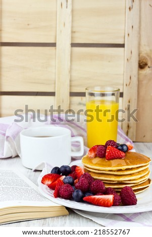 Delicious pancakes on wooden table with fruits and honey for breakfast selective focus - stock photo