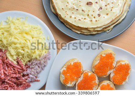 Delicious pancakes, sausage, cheese and sandwiches with red cavi - stock photo