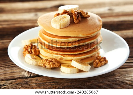 Delicious pancakes with banana on brown wooden background - stock photo