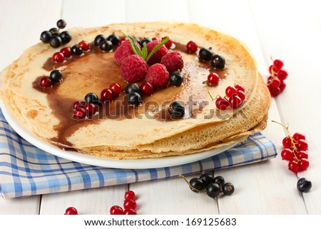 Delicious pancakes with berries and chocolate on plate on wooden table - stock photo