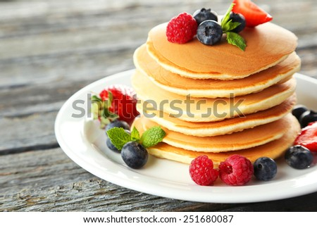 Delicious pancakes with berries on blue wooden background - stock photo
