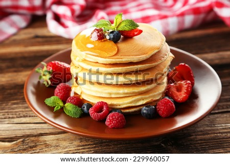 Delicious pancakes with berries on brown wooden background - stock photo