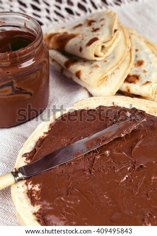 Delicious pancakes with nutella chocolate spread breakfast. Knife spreading chocolate cream on a crepe - stock photo