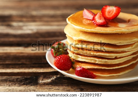 Delicious pancakes with strawberry on brown wooden background - stock photo
