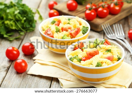 Delicious pasta in bowl on grey wooden background - stock photo