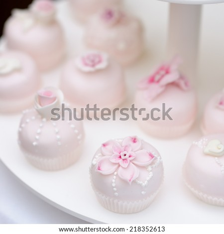 Delicious pink wedding cupcakes and cakes decorated with flowers - stock photo